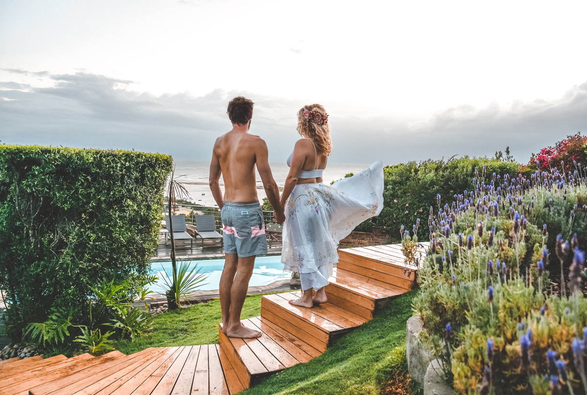 A couple staying at La Vista Lodge in Plettenberg Bay take in the view over the swimming pool towards the sea and mountains