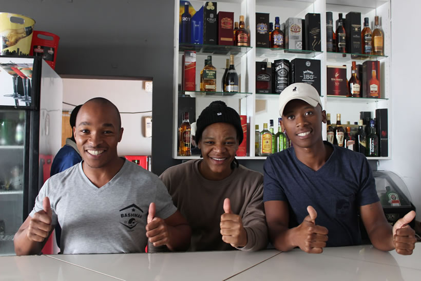 Ex, Lwand and Brian behind the bar at Skhulu's Lounge in KwaNokuthula, Plettenberg Bay