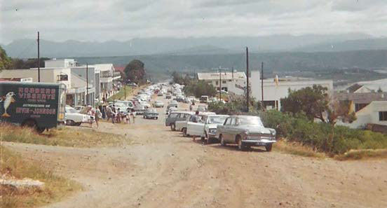 View down old Plett Main Street, with Robberg 'Visserye' delivery truck, circa 1967. Photo by CJ Morris.