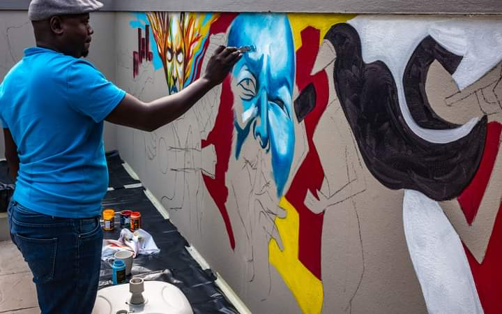 Artist William painting a mural at Brackenridge