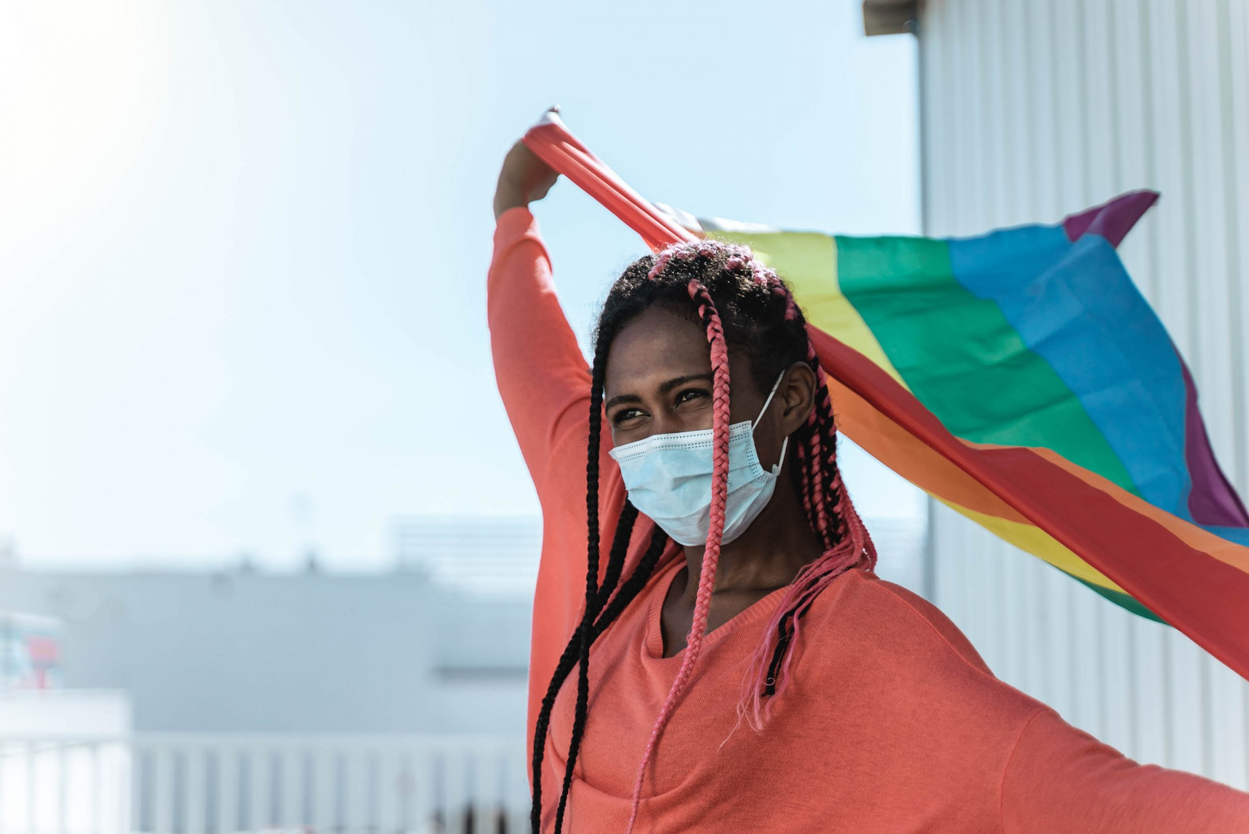 Young african lesbian with safety mask holding lgbt rainbow flag at pride event - Focus on face