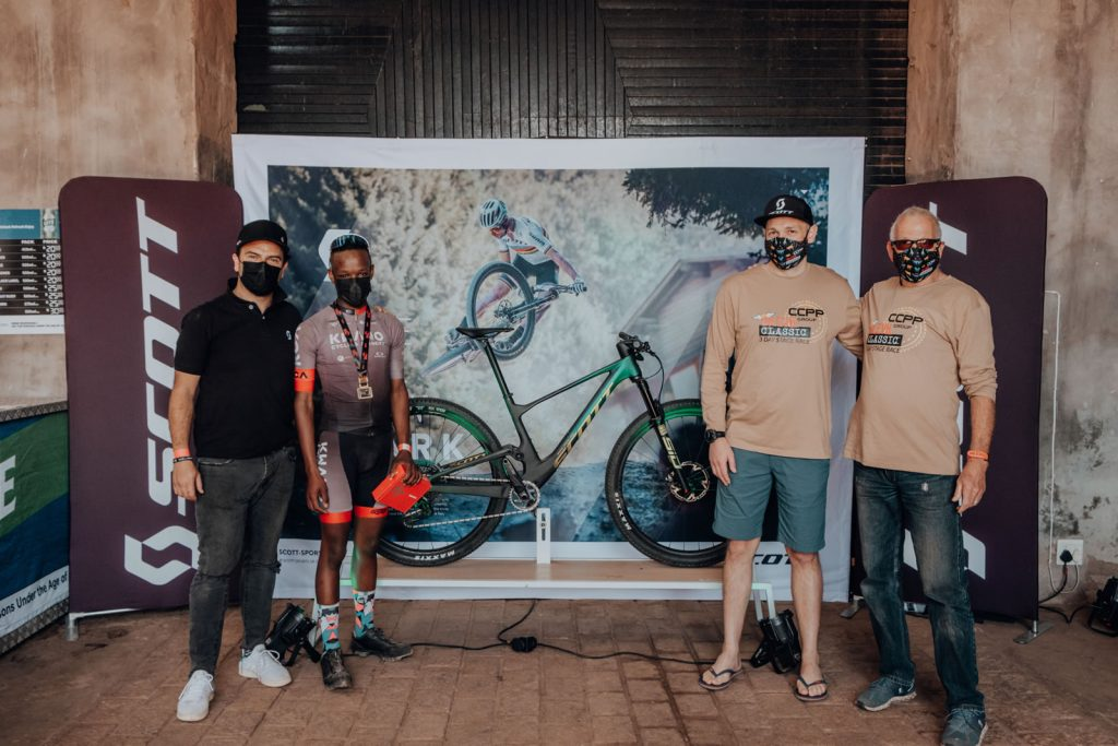 KWANO Cycling Academy alumni, Anelisa Aries, wins the SCOTT SPARK RC 900 TEAM AXS bike worth over R100 000. Left Joggie Prinsloo / Scott Sports Africa, Anelisa Aries (Kwano Cycling Academy), Clint Cawood (CEO CCPP Group) and Leon Evans aka Dr Evil.
